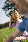 Man and woman sitting on meadow