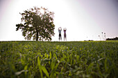 Couple jumping on meadow, raising arms