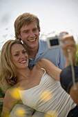 Couple on meadow taking picture, woman holding digital camera