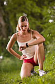 Female jogger kneeling on grass and looking at wristwatch