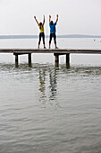 Two people standing on jetty, arms raised