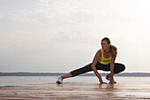 Young woman stretching on jetty before jogging