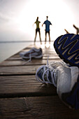 Two people standing on jetty, after jogging