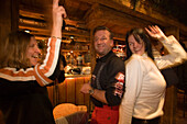 Two girls and a man dancing and enjoying an Apres-ski party at Purzelbaum Alm, Flachau, Salzburger Land, Austria