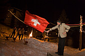 A flagswinger and swiss horn players at night, Saas-Fee, Valais, Switzerland
