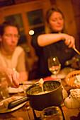 People having a cheese fondue, Fondue Hut of the Restaurant and Hotel Hohnegg, Saas-Fee, Valais, Switzerland