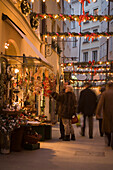People standing in front of a shop at the christmassy decorated Goldgasse in the evening, Salzburg, Salzburg, Austria