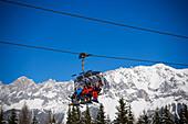 Skiers using the chair lift, Dachstein Mountains at horizon, Hochwurzen, Schladming, Ski Amade, Styria, Austria