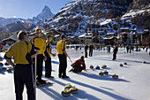 Group of men curling on a rink, Matterhorn in background, Zermatt, Valais, Switzerland (Curling: A rink game where round stones are propelled by hand on ice towards a tee (target) in the middle of a house (circle)).