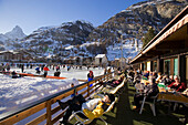 Visitors enjoying a curling game, Matterhorn in background, Zermatt, Valais, Switzerland (Curling: A rink game where round stones are propelled by hand on ice towards a tee (target) in the middle of a house (circle)).