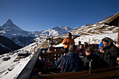 Group of people sitting on terrace of Restaurant Paradies (2540 m) and drinking champagne, Matterhorn (4478 m) in background, Findeln, Zermatt, Valais, Switzerland
