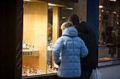 Couple standing in front of a shop window of a jeweller, Bahnhofstrasse, Zermatt, Valais, Switzerland