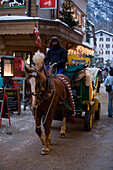 Carriage passing shopping street Bahnhofstrasse, Zermatt, Valais, Switzerland