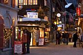 People walking over the illuminated shopping street Bahnhofstrasse in the evening, Zermatt, Valais, Switzerland