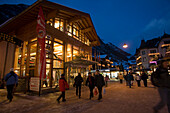 People walking over the shopping street Bahnhofstrasse in the late evening, Zermatt, Valais, Switzerland