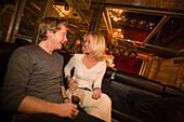 Couple sitting on lounge and laughing, Vernissage Club, Design by Heinz Julen, Zermatt, Valais, Switzerland