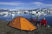 Mountainbiker cooking near his tent, Camping, Jokulsarlon, Glacier lake, Iceland
