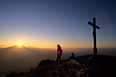 Mountaineer and cross on the summit of Heuberg with sunset over the Wendelstein range, Bavarian Alps, Upper Bavaria, Bavaria, Germany