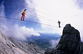 Two mountaineers meeting halfway on a rope bridge, Koppenkarstein west ridge, Dachstein range, Upper Austria, Austria