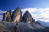 Mountaineer on a pinnacle in front of Drei Zinnen, Dolomites, South Tyrol, Italy