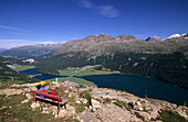 Hiker resting on a red bench with views to the Engadin lakes, St. Moritz and Bernina Mountain range, Upper Engadin, Grisons, Switzerland