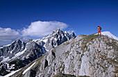 Hiker on Roetelstein with Hochkesselkopf, Torstein and Dachstein in the background, Dachstein mountain range, Salzburg, Austria