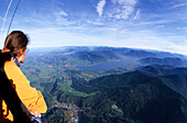 View from the basket of a hot air balloon to Gmund and lake Tegernsee with young woman in foreground, Bavarian alps, Upper Bavaria, Bavaria, Germany