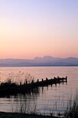 Landing stage in Gstadt at dawn with Hochstaufen and Zwiesel, lake Chiemsee, Chiemgau, Upper Bavaria, Bavaria, Germany