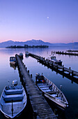 Landing stage and boats in Gstadt at lake Chiemsee at dawn with Fraueninsel, Hochgern and Hochfelln in the background, Chiemgau, Upper Bavaria, Bavaria, Germany