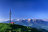Red bench and cross on the summit of Wandberg with view to Wilder Kaiser and Zahmer Kaiser, Chiemgau alps, Tyrol. Austria
