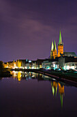 View over Trave River to old town at night, Schleswig-Holstein, Germany