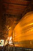 View along the golden Reclining Buddha, Wat Pho, The Temple of the Reclining Buddha, the largest and oldest wat in Bangkok, Bangkok, Thailand