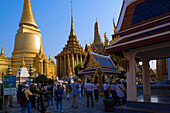 Group of tourists visiting the Wat Phra Kaew, the most important Buddhist temple of Thailand, Phra Sri Rattana Chedi and Phra Mondop, the library in background, Ko Ratanakosin, Bangkok, Thailand