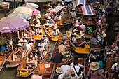 Tourists in wooden boats visiting the Floating Market, Damnoen Saduak, near Bangkok, Ratchaburi, Thailand