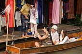 Female tourist in a wooden boat choosing a dress at a stand at Floating Market, Damnoen Saduak, near Bangkok, Ratchaburi, Thailand