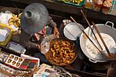 Woman offering food and souvenirs at Floating Market, Damnoen Saduak, near Bangkok, Ratchaburi, Thailand