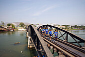 Boys walking over the River Kwai Bridge, built by prisoners of World War II of the Japanese, Kanchanaburi, Thailand