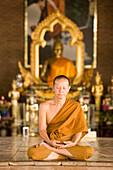 Buddhist monk praying in front of the Golden Jubilee Buddha Image, placed in the Chao Khun Maha Bua Yannasampanno 84-year Campassion Pavilio, Wat Pa Luangta Bua Yannasampanno Forest Monastery, Tiger Temple, Kanchanaburi, Thailand
