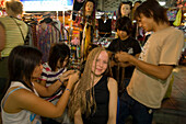 Female tourist getting al lot of afro braids, takes up to 4 hours at a hairdressing stand at Th Khao San Road in the evening, Banglamphu, Bangkok, Thailand