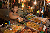 Woman preparing fresh food at a  stand at Th Khao San Road in the evening, Banglamphu, Bangkok, Thailand