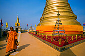 Monk visiting gilded Chedi, housed a Buddha relic of the Wat Saket on the Golden Mount, Bangkok, Thailand