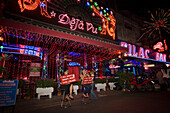 """Women sitting in front of Go-go bar """"DeJa Vu"""" and presenting signs, Soi Cowboy, a red-light district, Th Sukhumvit, Bangkok, Thailand"""