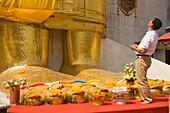 Man looking up to the gilded Buddha statue, 32 m high, Wat Intharawihan, Banglamphu, Bangkok, Thailand