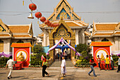 People visiting Wat Suthat, decorated for the Chinese New Year, Bangkok, Thailand