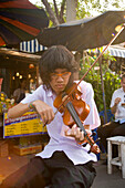 Young woman playing the violin at Suan Chatuchak Weekend Market, Bangkok, Thailand