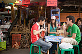Three young people sitting at a table near a food stall, one eating ice cream, Suan Chatuchak Weekend Market, Bangkok, Thailand