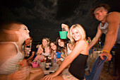 Young people at a Full Moon Party, girl holding a small pail, Hat Rin Nok, Sunrise Beach, Ko Pha-Ngan, Thailand