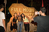 Young people taking a picture in front of an stone with an inscription, Full Moon Party, Hat Rin Nok, Sunrise Beach, Ko Pha-Ngan, Thailand