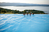 Children resting on pool edge, bay of Porto Vecchio, Southern Corse, France