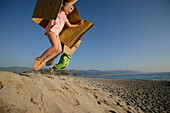 Two children  jumping from dune, Liamone Beach, Western Corse, France